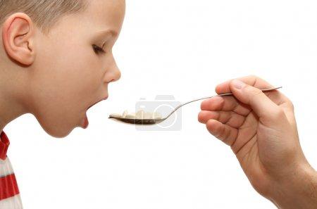 Child taking medicine on white background