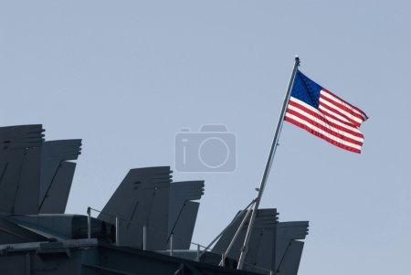 Photo pour Les étoiles et les rayures volant à l'arrière du porte-avions kitty-hawk - image libre de droit