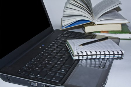 Laptop computer, pen and books
