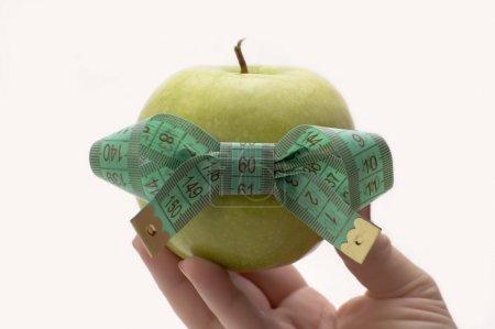 Photo pour Pomme verte avec ruban à mesurer à la main . - image libre de droit