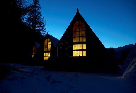 Photo pour Petites maisons couvertes de neige la nuit dans les montagnes - image libre de droit