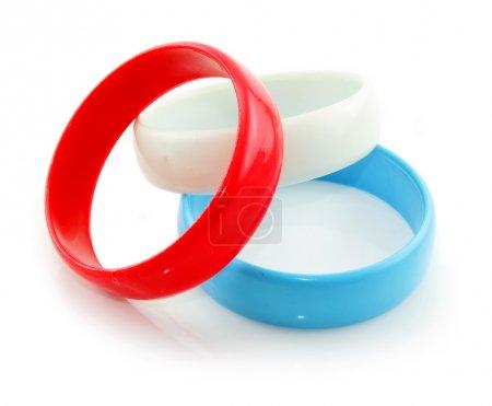 Foto de Tres brazaletes de plástico coloreados aislados sobre un fondo blanco - Imagen libre de derechos