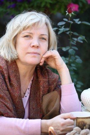Photo pour Femme du Moyen Age Boire du thé dans le jardin - image libre de droit