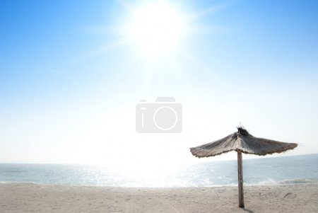 Photo for Beautiful panorama of a beach with a beach umbrella and the shining sun - Royalty Free Image