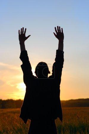 Photo pour Prier la silhouette de l'homme sur fond de coucher de soleil - image libre de droit