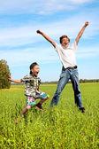 Teenager and kid jumping