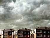 Houses against dark clouds