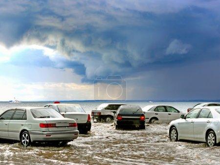 Photo pour Inondations dans la ville avec des voitures et la conduite dans l'eau - image libre de droit