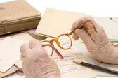 Old hands hold glasses, Pencil, letter