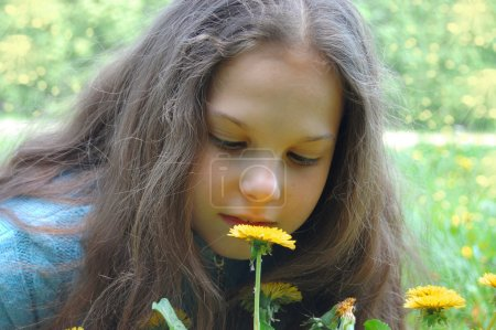 Young girl Looking on dandelion flower