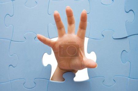 Photo pour Main féminine à travers un puzzle - image libre de droit