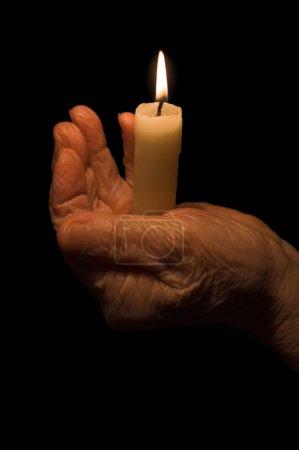 Photo pour Vieilles mains féminines avec une bougie - image libre de droit