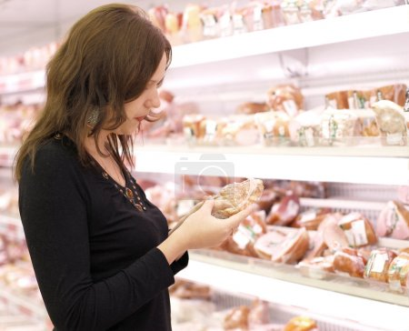 Girl buys meat in a supermarket