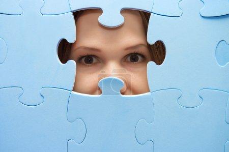 Photo pour La fille espionne à travers un puzzle bleu - image libre de droit
