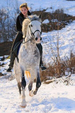 Girl on white dressage horse in winter