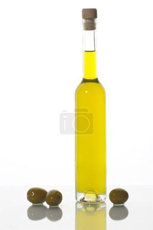 Foto de Botella de aceite de oliva y tres aceitunas aislados en blanco. - Imagen libre de derechos