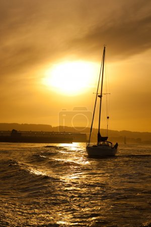 Sunset at sea with yacht silhouette