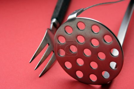 Fork and potatoe-masher on red...