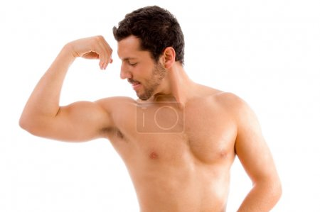 Strong man looking at his muscles