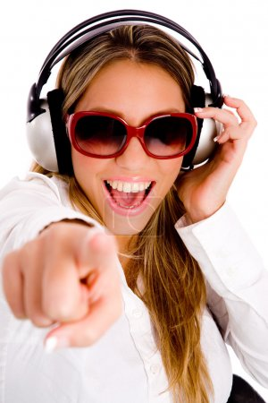 Photo pour Vue de face de la femme pointant jouissant de la musique sur un fond isolé - image libre de droit