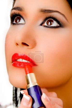 Portrait of beautician applying lipstick