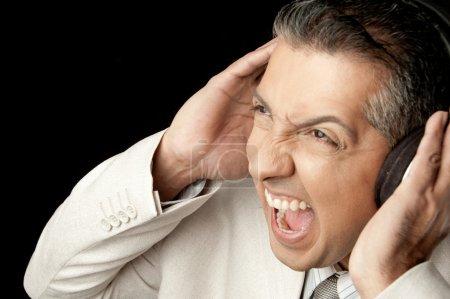 Photo pour Homme d'affaires, l'écoute de la musique forte avec les mains sur ses oreilles - image libre de droit