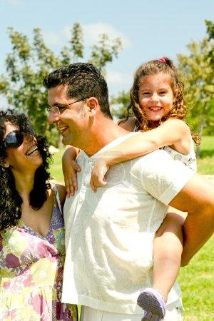 Photo pour Homme souriant parlant à sa femme avec sa fille sur le dos - image libre de droit