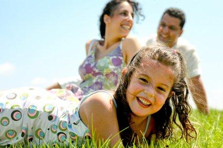 Photo pour Gros plan du jeune enfant avec ses parents qui se détendent à l'arrière - image libre de droit