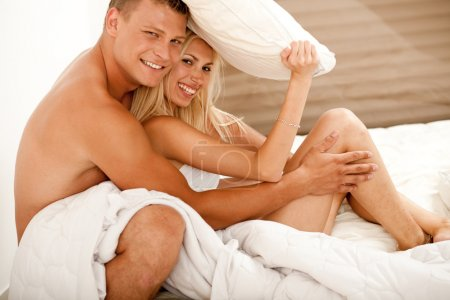 Attractive amorous couple in bedroom