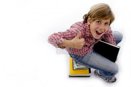 Top view of boy sitting on pile of books