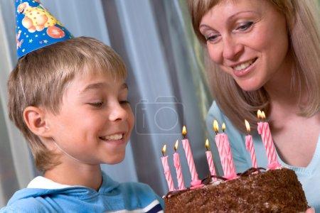 Photo pour Garçon dans son anniversaire, maman et son fils fête, chapeaux, tarte aux bougies - image libre de droit