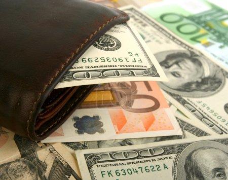 100 dollar bill in leather brown purse