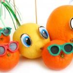 Funny orange, lemon and mandarins on white backgro...