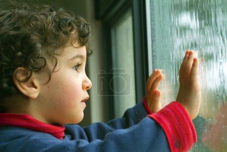Photo pour Petit garçon regardant la pluie par la fenêtre - image libre de droit