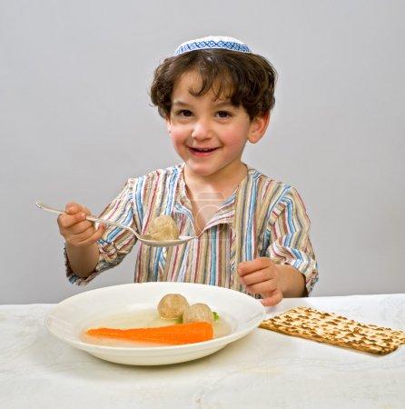 Photo pour Juif jeune garçon ayant matzo boule soupe - image libre de droit