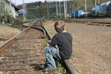 Boy sitting on rail track