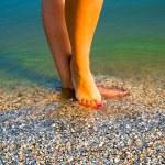 Girls feet in sea water...