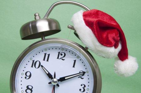 Foto de Poco tiempo antes de la temporada de vacaciones. reloj con santa sombrero tradicional rojo y verde. - Imagen libre de derechos