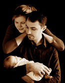Parents with newborn baby in sepia