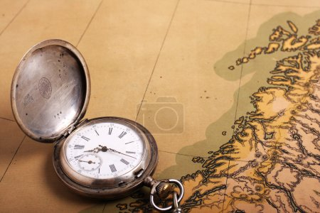 Old silver watch on ancient map