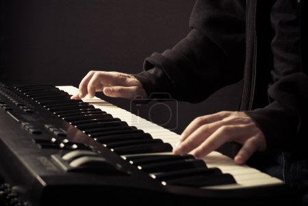 Photo pour Les mains du bel homme sur les clés du synthétiseur - image libre de droit