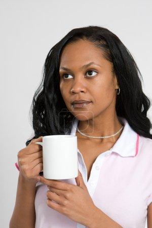 Photo pour Une jeune femme d'affaires afro-américaine d'humeur contemplative tout en buvant du café . - image libre de droit