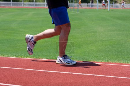 Photo for A man runs the track for the cardiovascular benefits. - Royalty Free Image