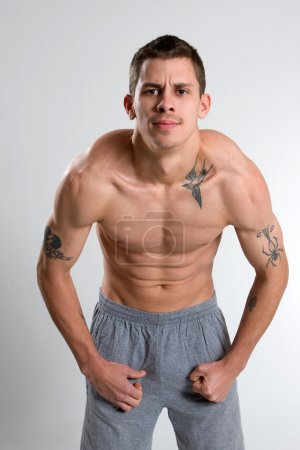 Tattooed Man Flexing Muscles