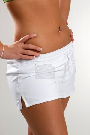 Photo for A trim young woman shows off her waistline in white shorts. - Royalty Free Image