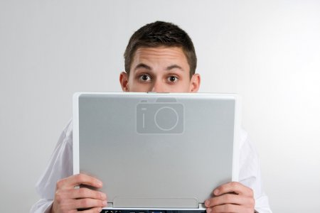 Young Man Peeking Over Laptop Computer