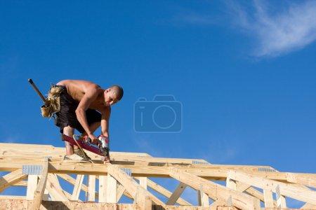 Photo pour Charpentier utilise une cloueuse pneumatique pour attacher les accolades et les chevrons à un système de toiture sur une maison neuve en construction. - image libre de droit