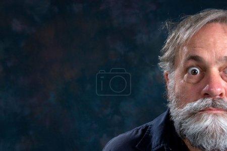 Half the face of a bug eyed mature man with beard....