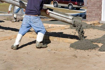 Photo pour Un ouvrier de la construction ordonne à une goulotte de couler du béton pour une allée sur un nouveau site d'habitation . - image libre de droit
