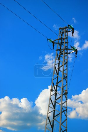 A tall electric pillar in the blue sky